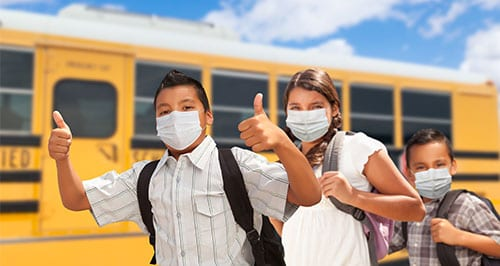 Kids wearing masks with thumbs up in front of school bus