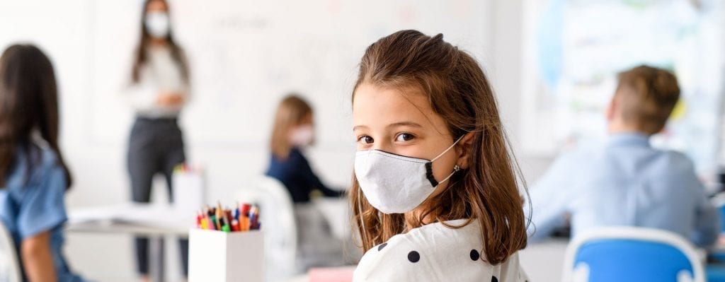 Texas public school class room with child wearing a mask for safety against viral infection